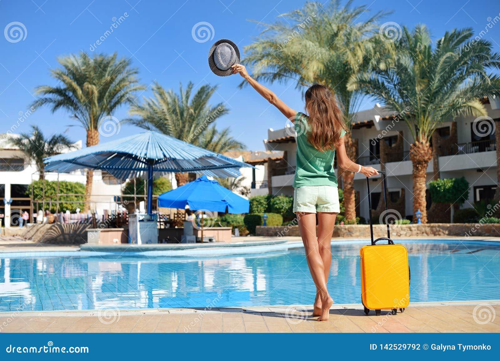 Podróż, wakacje letni i urlopowy pojęcie, - Piękna kobieta chodzi blisko hotelowego basenu terenu z żółtą walizką w Egipt