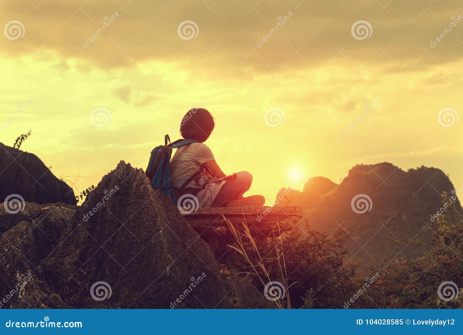 Podróżnika obsiadanie na odgórnej górze z przyglądającym zmierzchem