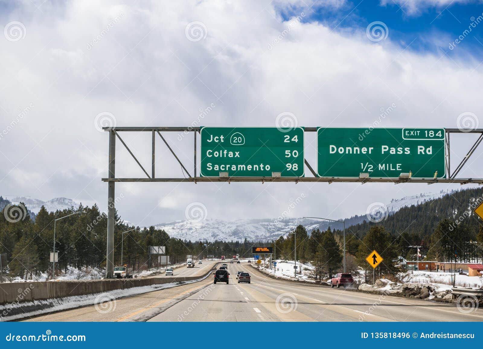 Podróżujący na międzystanowym przez sierry góra blisko do Jeziornego Tahoe; śnieg zakrywać burz chmury i góry; Truckee,