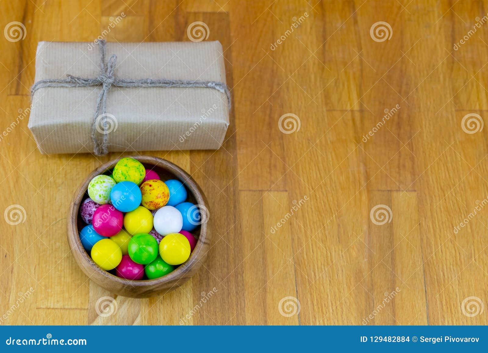 Podstawowy świąteczny prostokątny pudełko w brązu Kraft papierze z naturalną arkaną i pucharze cukierków dragees na drewnianym tl