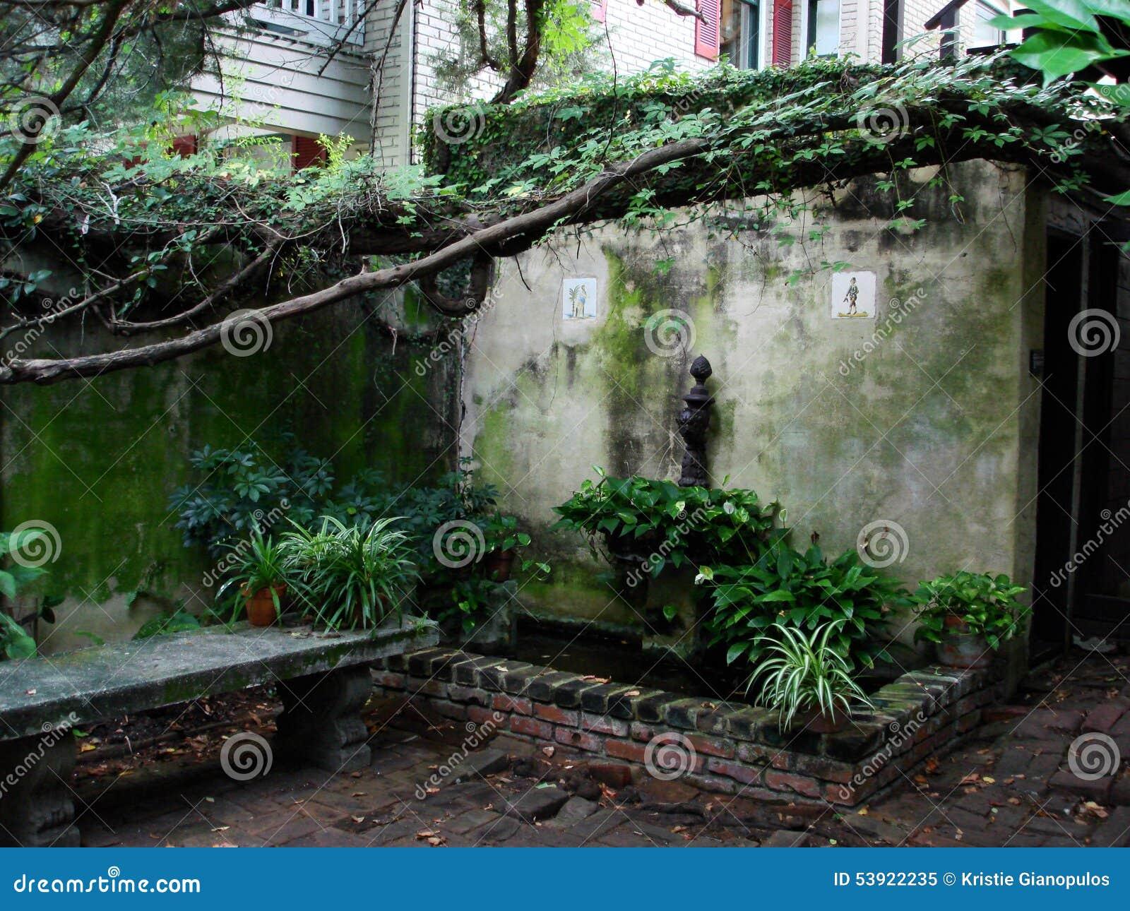Podwórze ogród z cegłami, kamienną ławką i winogradami,