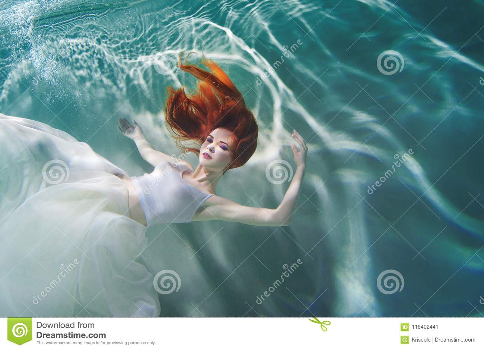 Podwodna dziewczyna Piękna miedzianowłosa kobieta w białej sukni, pływa pod wodą