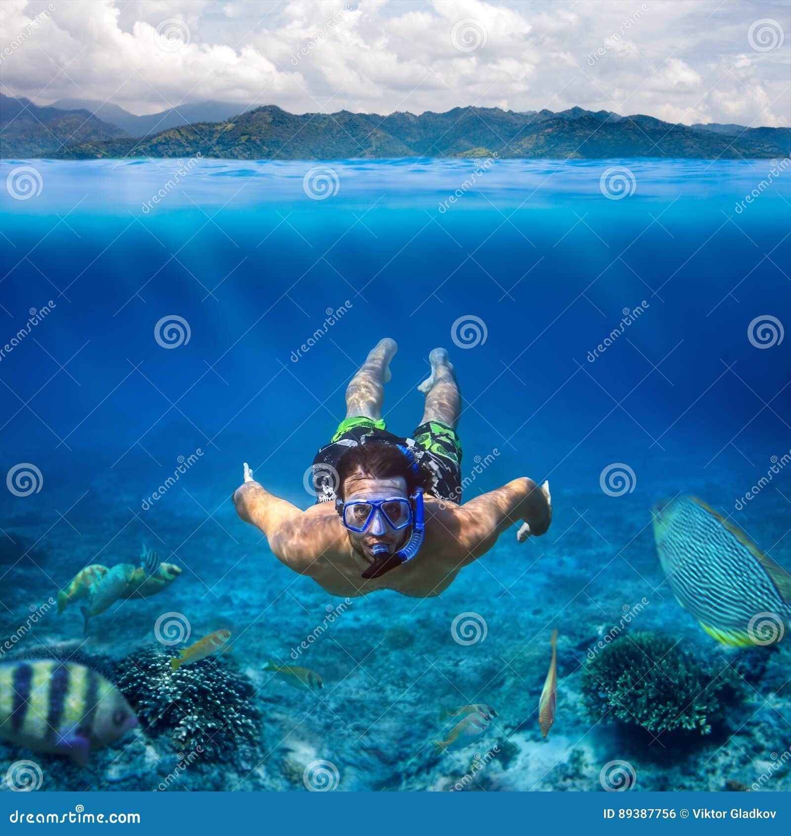 Podwodny krótkopęd młody człowiek snorkeling w tropikalnym morzu dalej