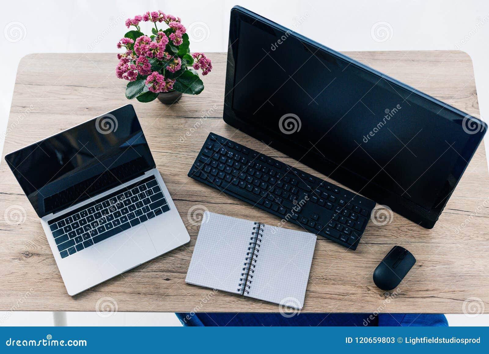 Podwyższony widok stół z kwiatami, pustym podręcznikiem, laptopem i komputerem,