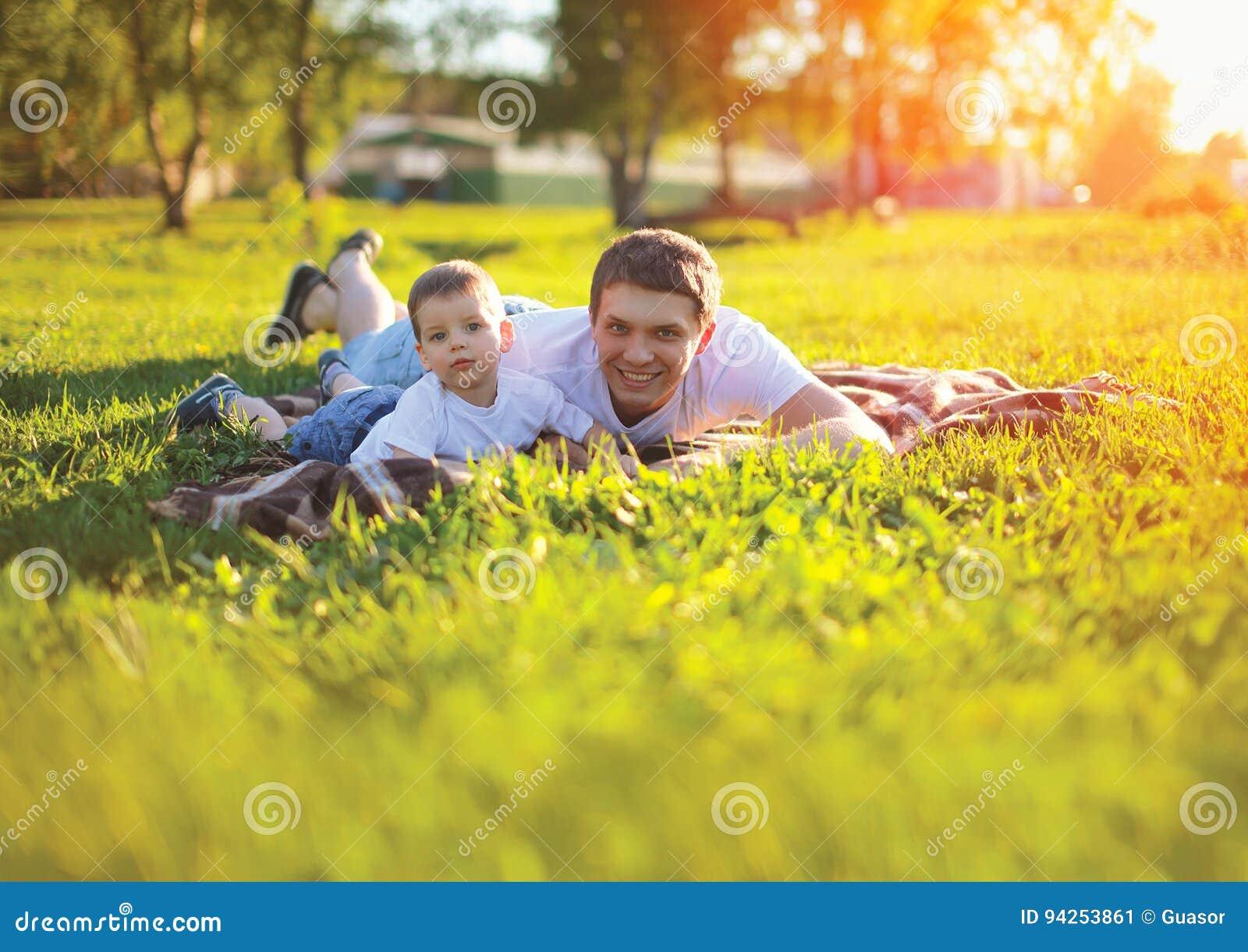 Pogodnego portreta szczęśliwy ojciec z syna dziecka lying on the beach na trawie