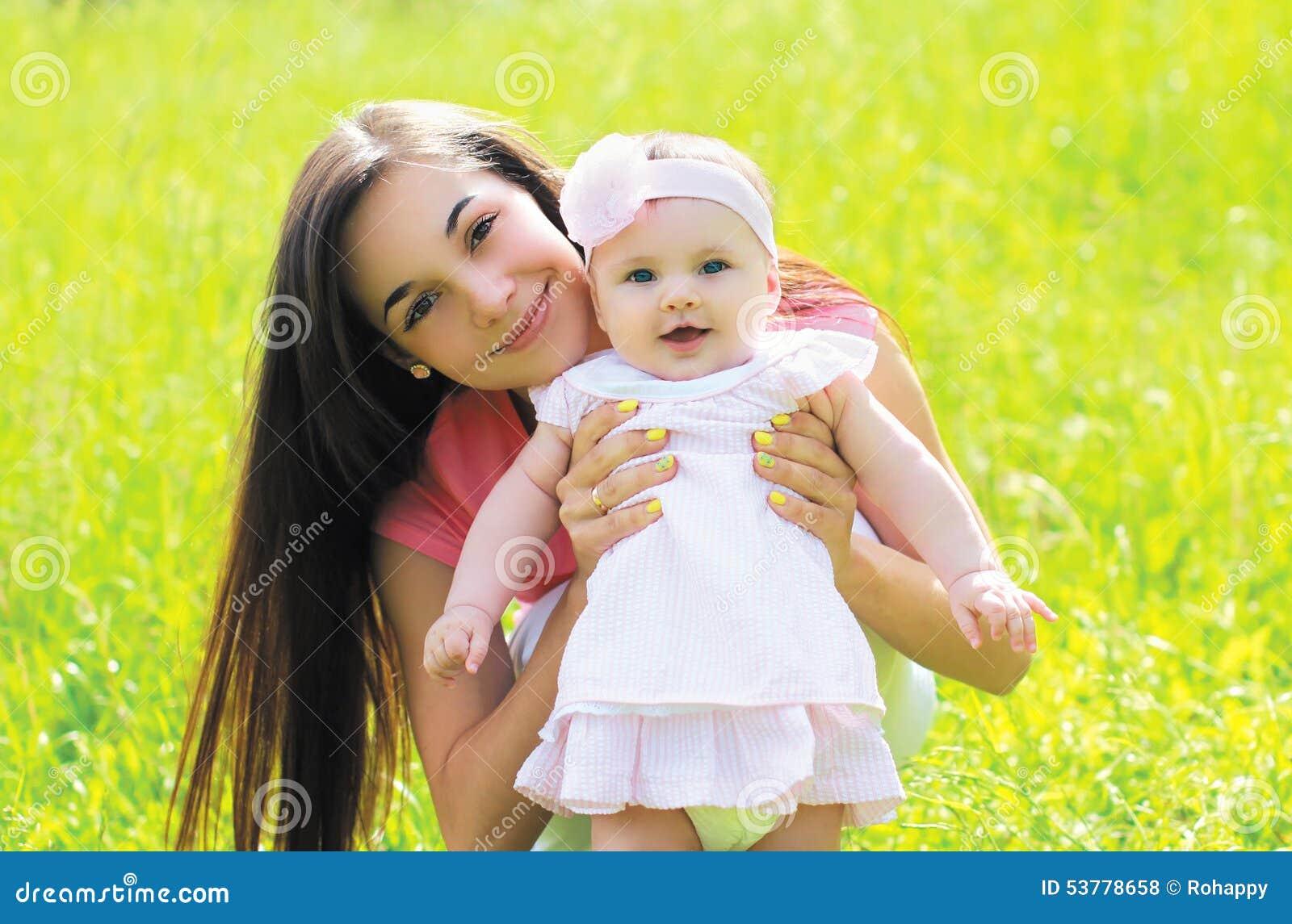 Pogodny portret szczęśliwa potomstwo matka z dzieckiem na trawie