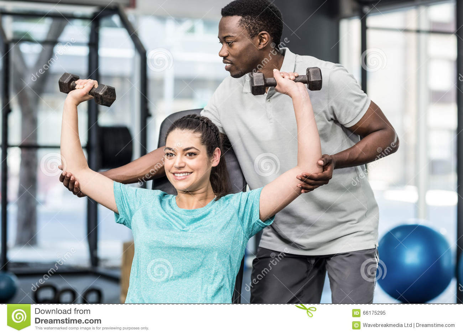 Poids de levage de femme sportive aidés par l entraîneur