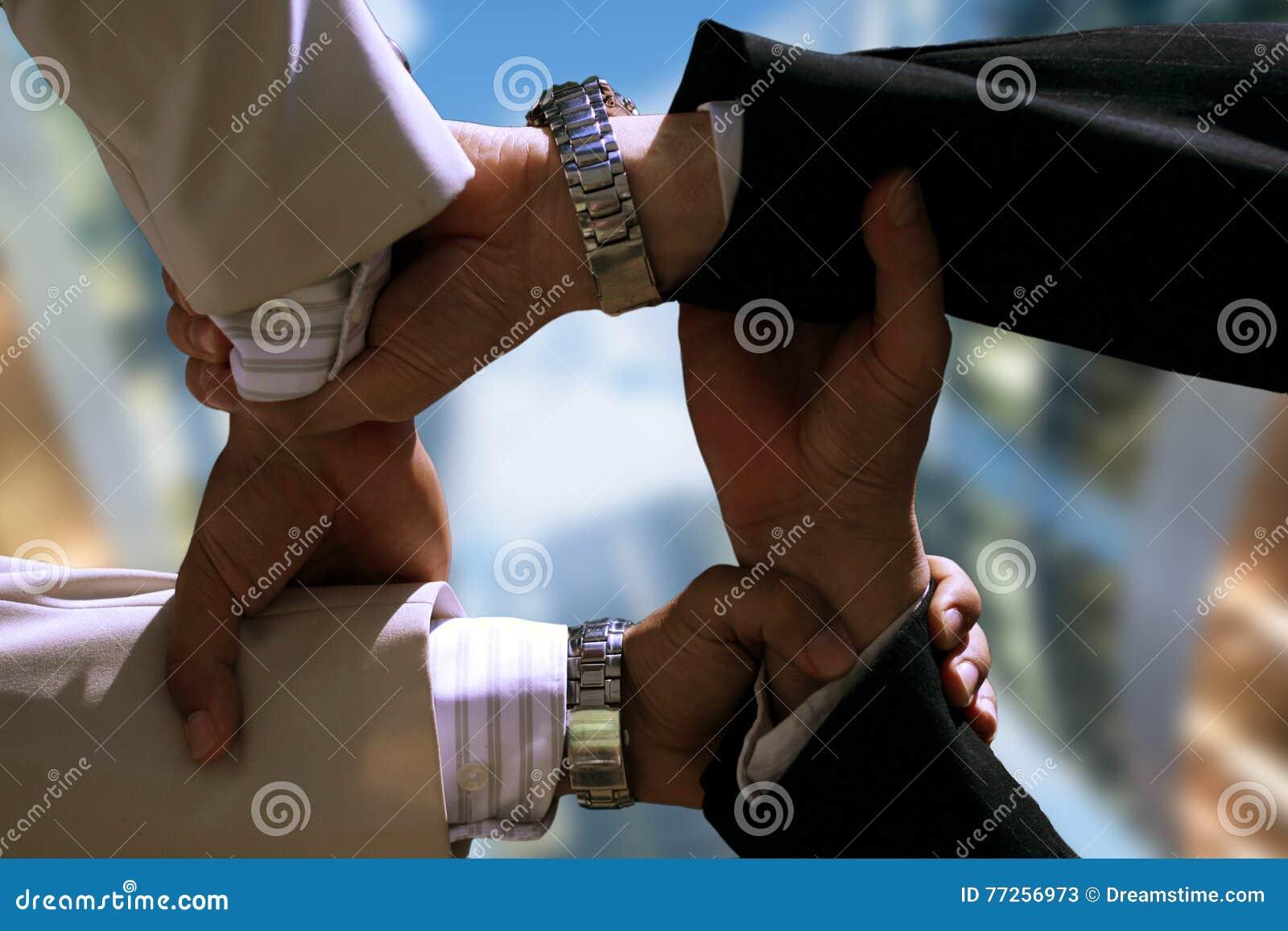 Poignée à quatre mains en gros plan des hommes d affaires