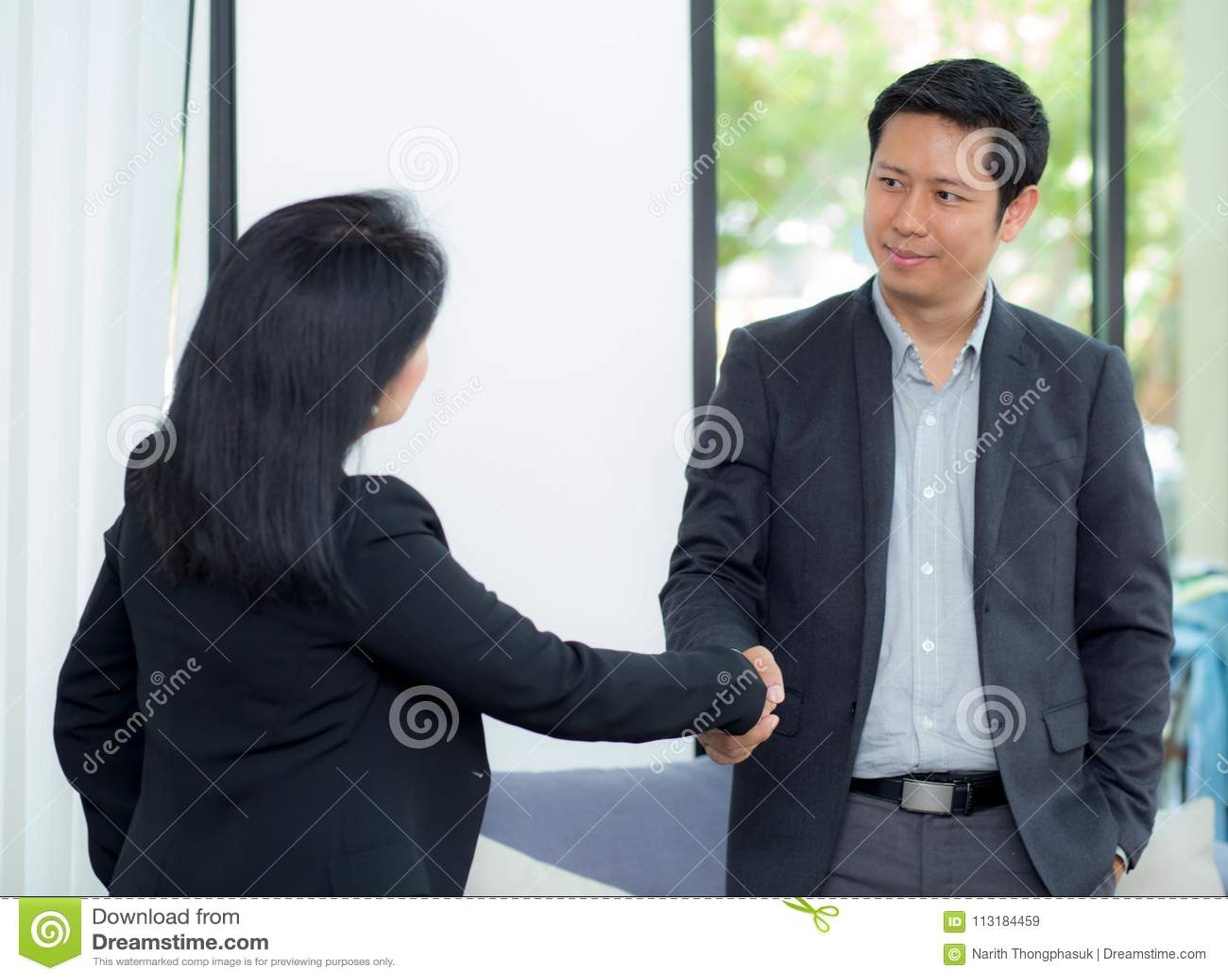 Poignée de main d homme d affaires et femme d affaires après la réunion d affaires réussie