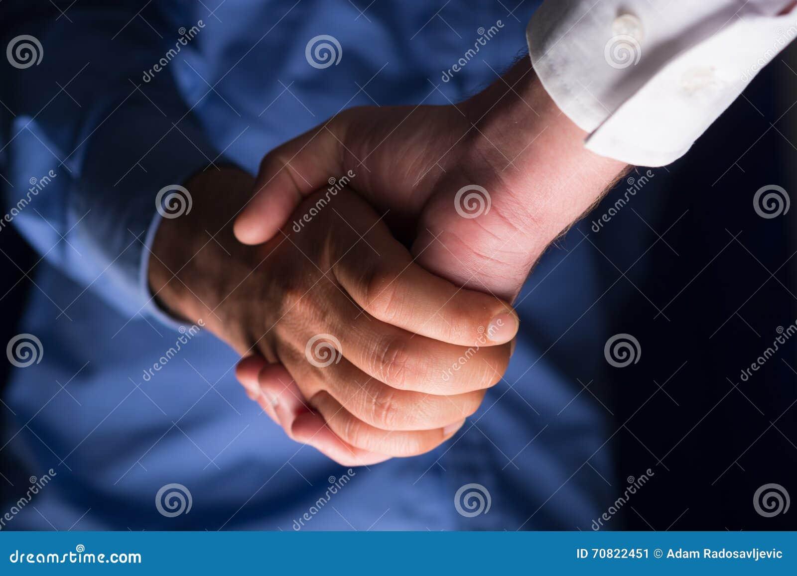 Poignée de main de poignée de main dans l obscurité avec la faible luminosité