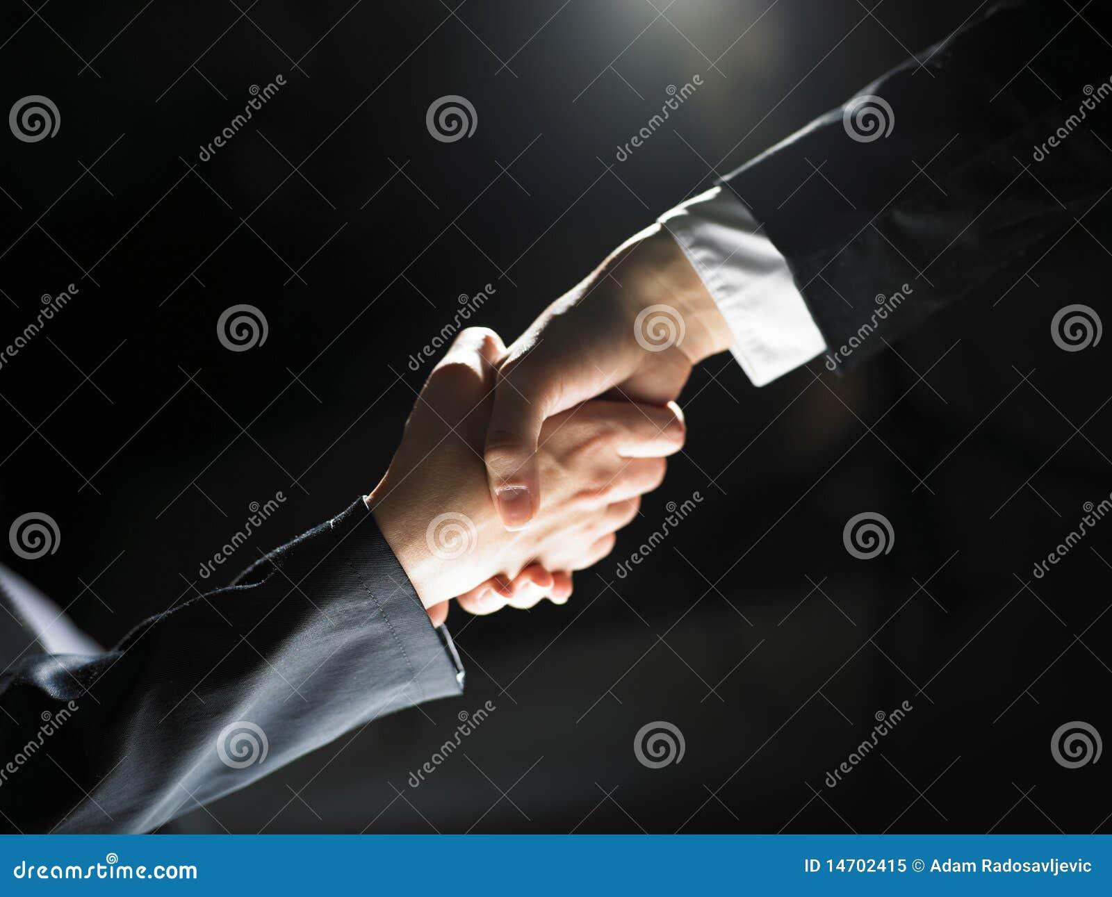 Poignée de main de prise de contact sur léger et l obscurité