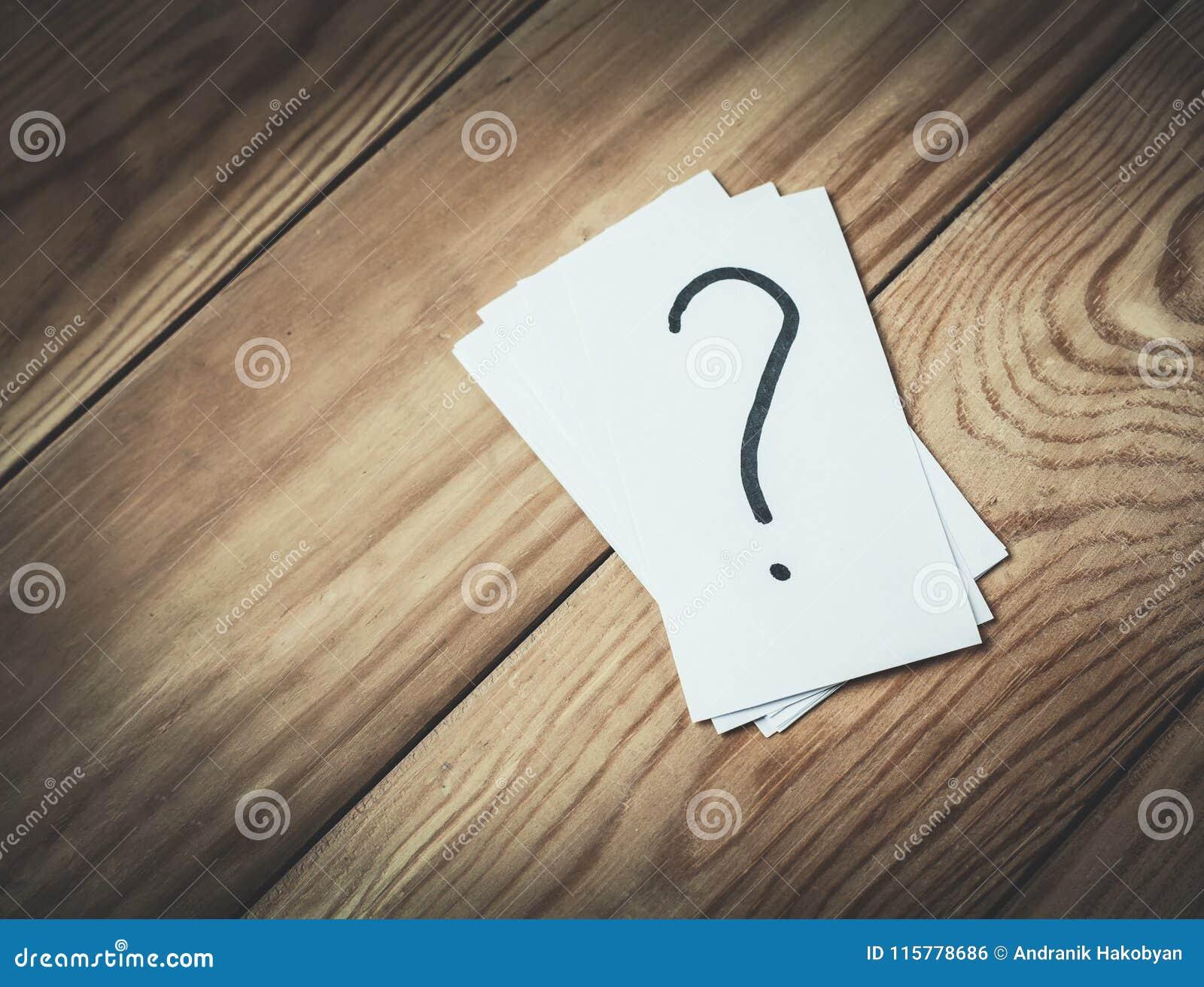 Point d interrogation en papier sur un fond en bois