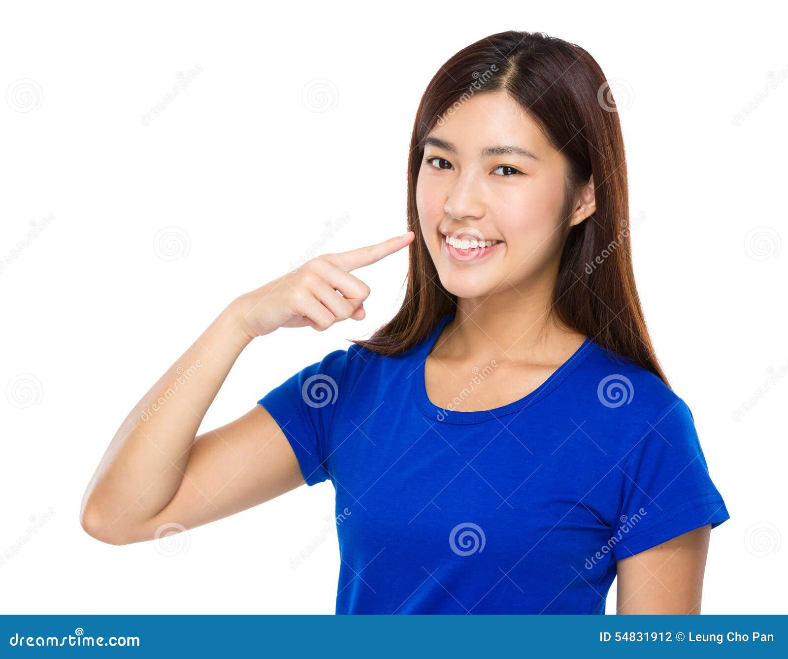 Point de doigt de femme à ses dents