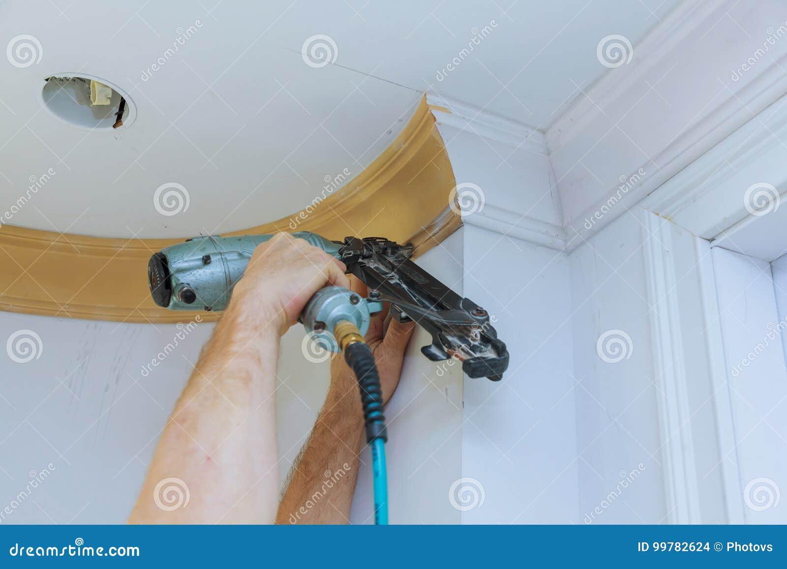 Pointe de charpentier utilisant l arme à feu de clou pour couronner l équilibre de encadrement de moulage, avec l étiquette de mi