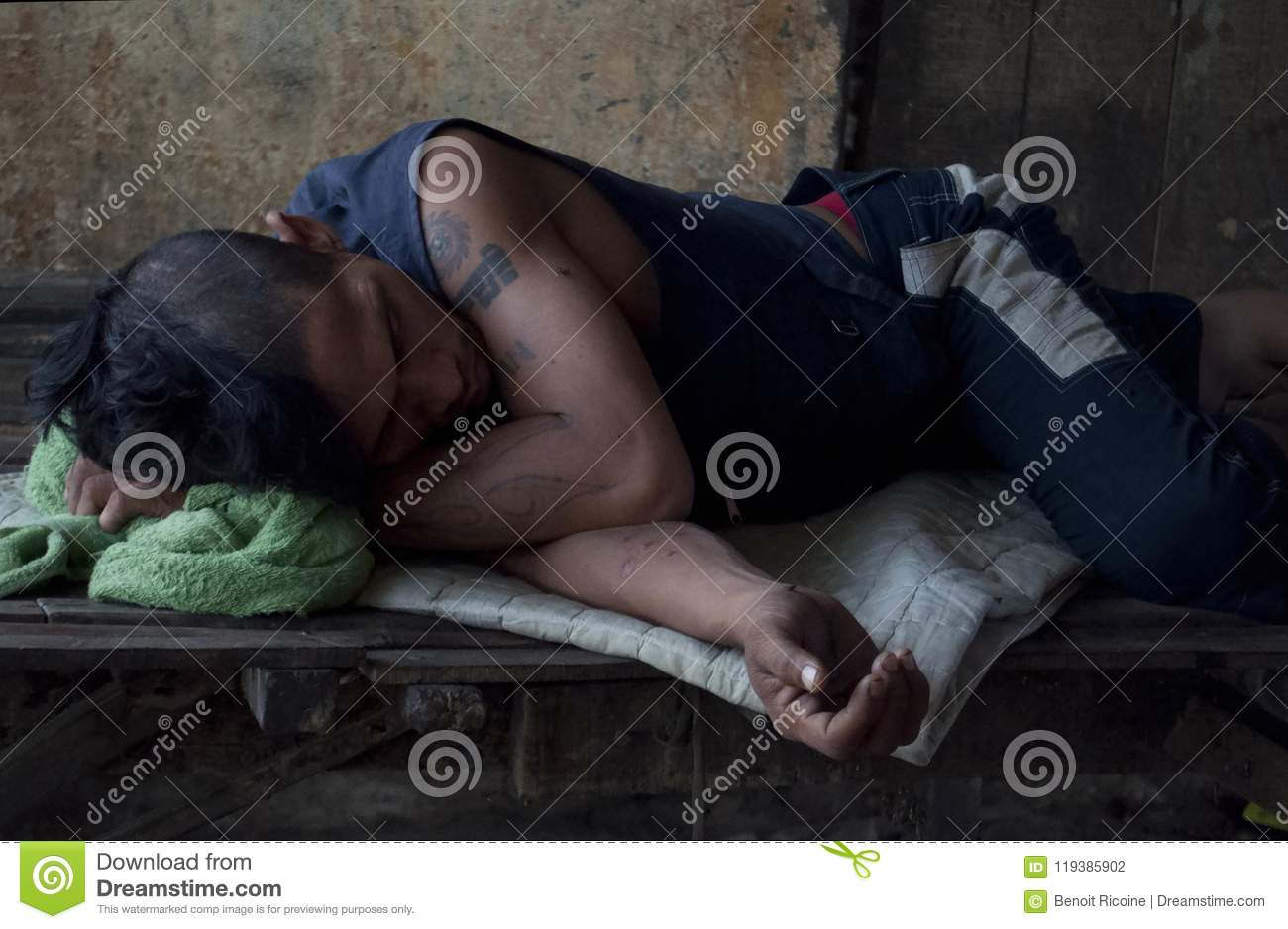 Poipet/Cambodia Sick homeless young man takes a nap at the abandoned train station