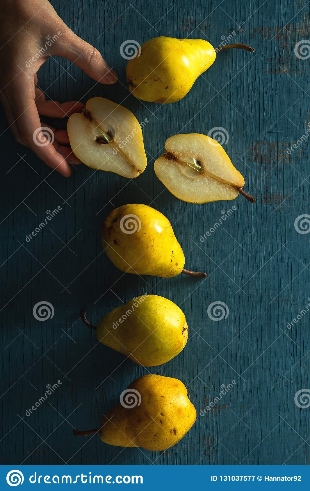 Poires jaunes sur un fond bleu en bois avec la main de femme