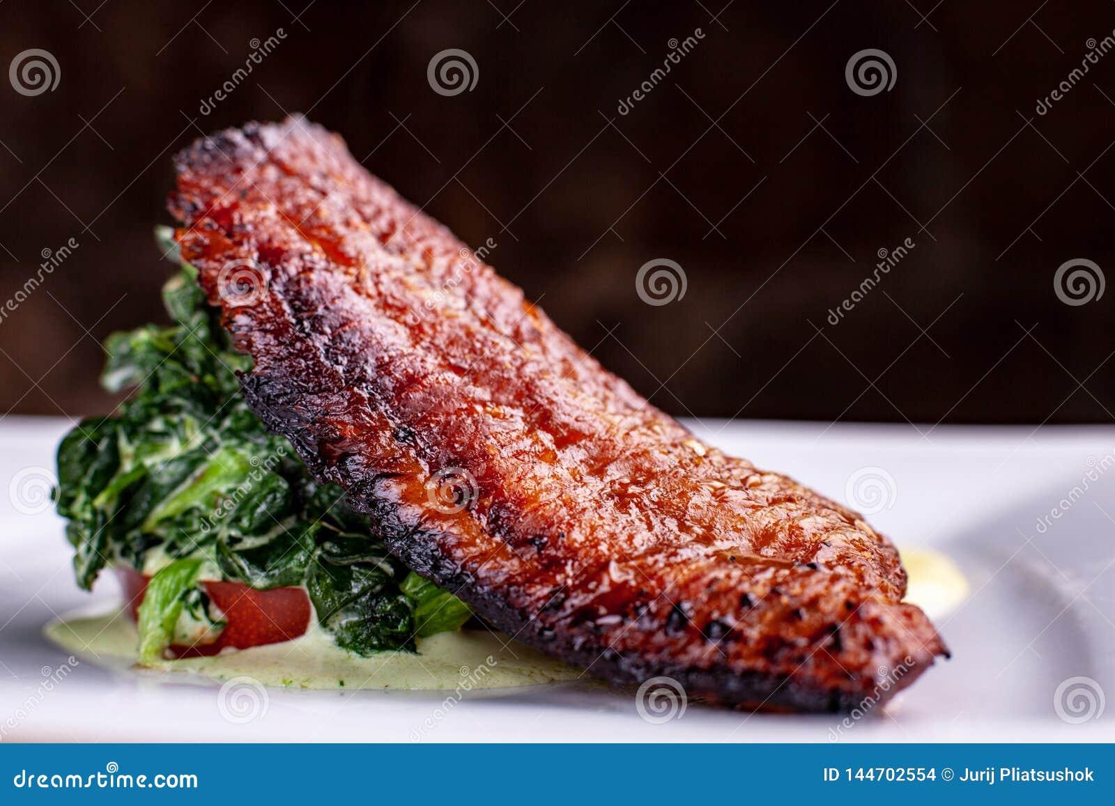 Poisson-chat frit par casserole avec de la sauce à épinard et blanche