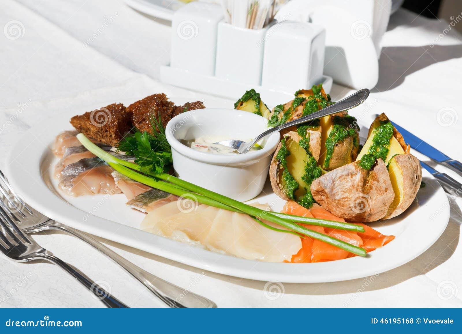 Poissons salés avec la pomme de terre cuite au four du plat blanc