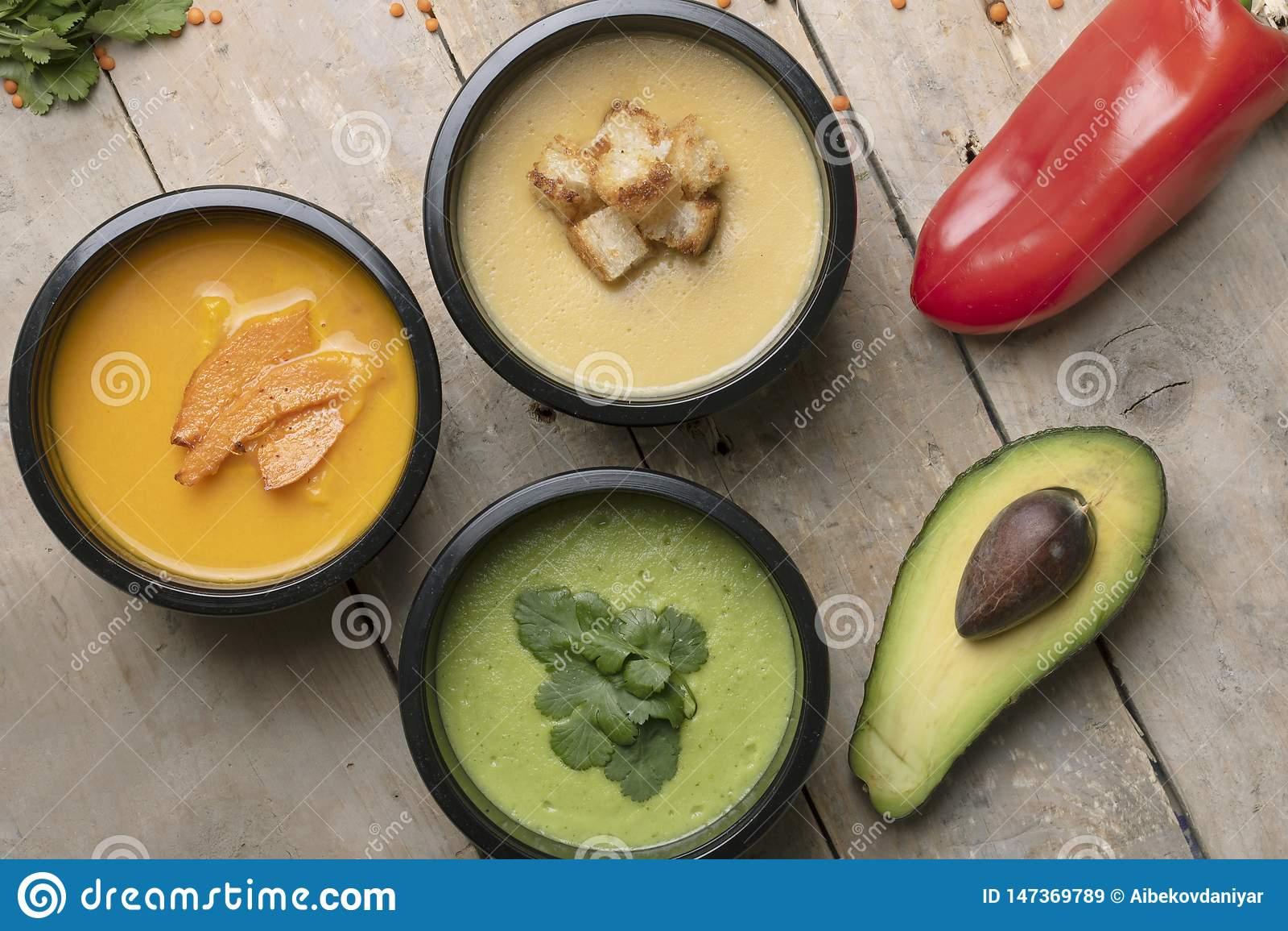 Poivron rouge, demi avacado et cuill?re pr?s des soupes ? vegan dans des conteneurs de nourriture, repas pr?t ? manger