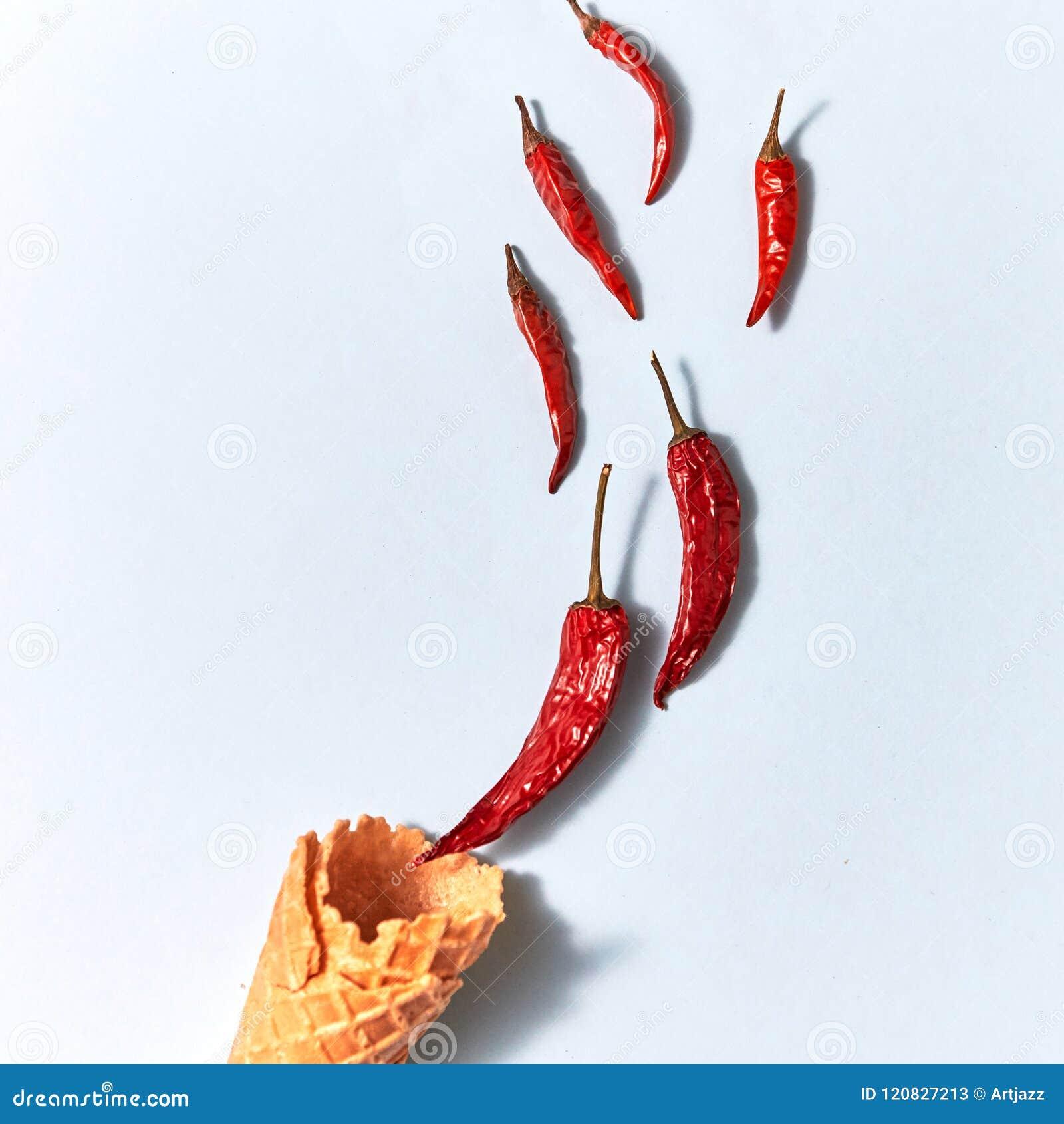 Poivrons de piment secs d un rouge ardent dans un cône de gaufrette sur le fond gris, vue supérieure