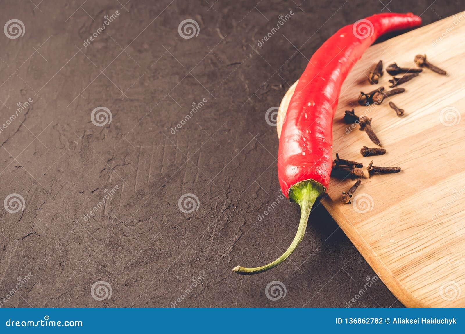 Poivrons et épices sur une planche à découper vide/poivrons de piment d un rouge ardent et épices d un rouge ardent de piment sur