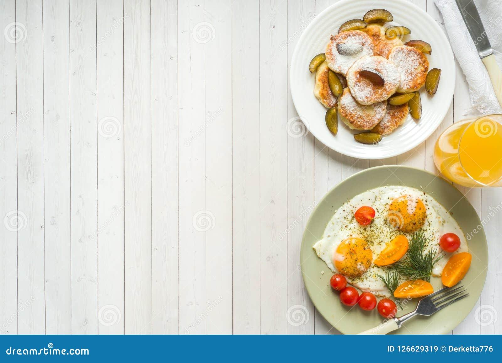 Pojęcie śniadanie Smażył jajka, chałupa sera bliny, śliwki i oatmeal z mlekiem, sok pomarańczowy na stole