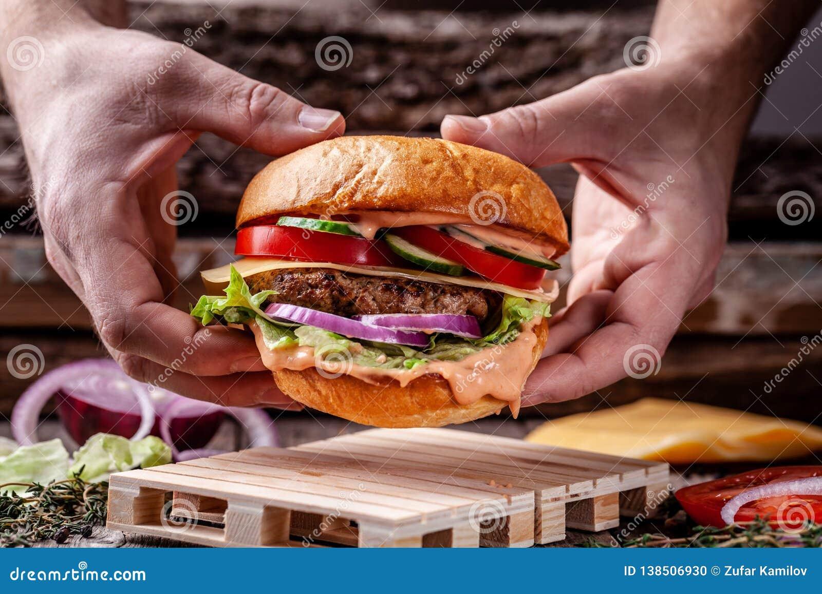 Pojęcie Amerykańska kuchnia Domowej roboty hamburger gotujący mężczyzną od babeczki, meaty wołowiny i wieprzowin cutlets, pomidor