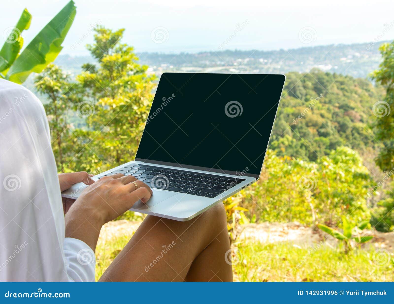 Pojęcie daleka praca lub freelancer styl życia Kaukaska kobieta z laptopu obsiadaniem przy tropikalnym punkt widzenia