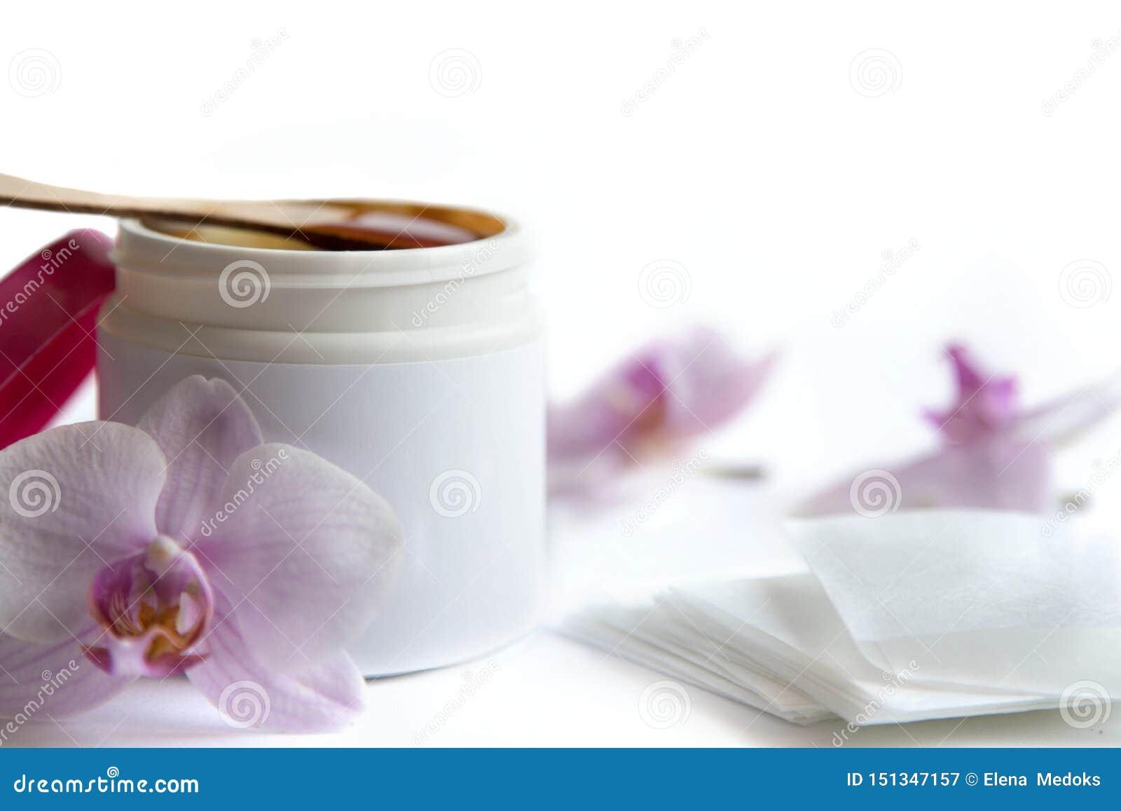 Pojęcie depilacja i piękno jest cukrowym pasty lub włosy usunięcia woskiem w białym plastikowym słoju z drewnianą wosk szpachelką