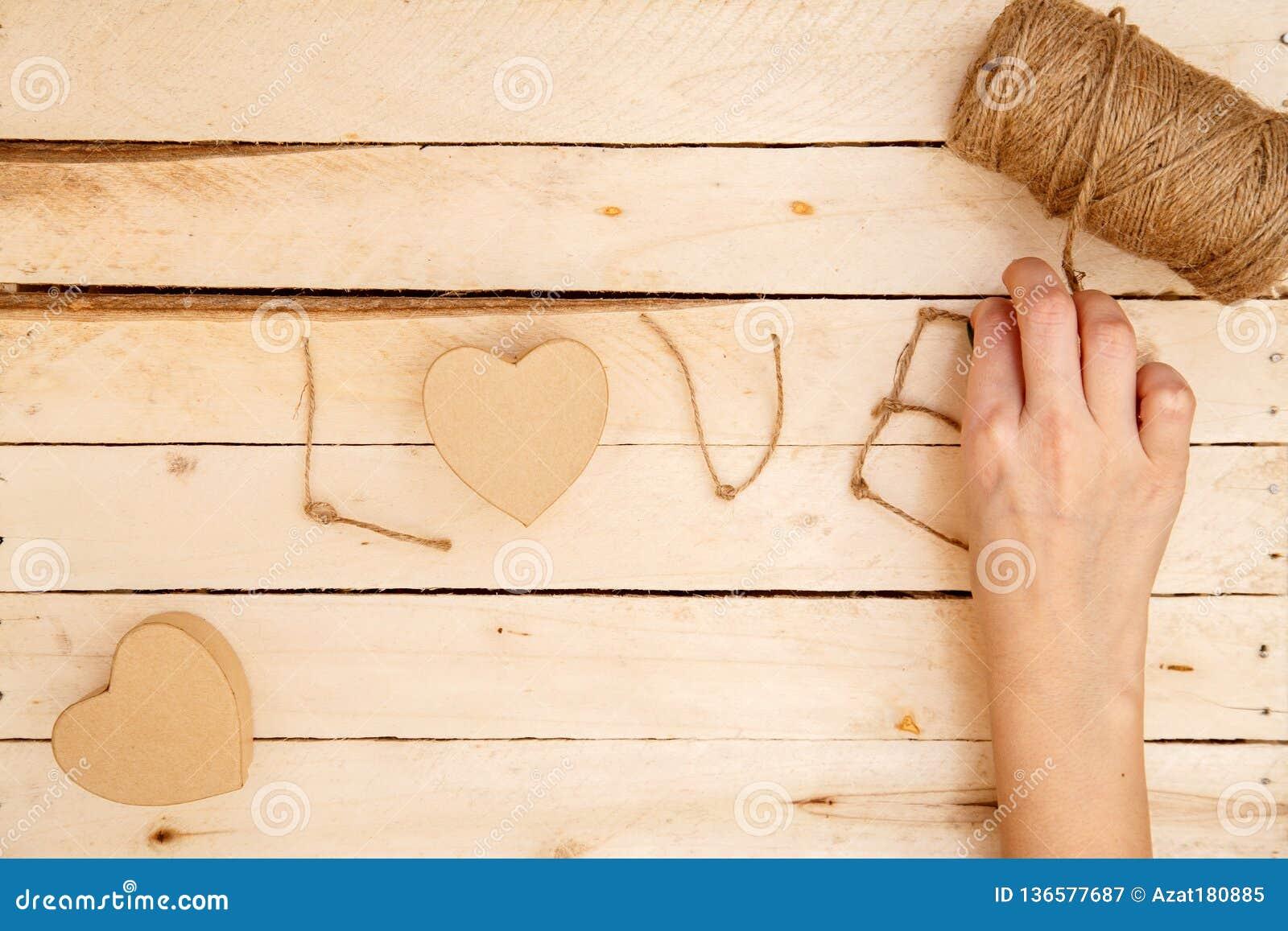 Pojęcie dla historii miłosnych dla walentynka dnia i Żeńskie ręki robią pudełkom w postaci serca i «miłości «wpisowej od a
