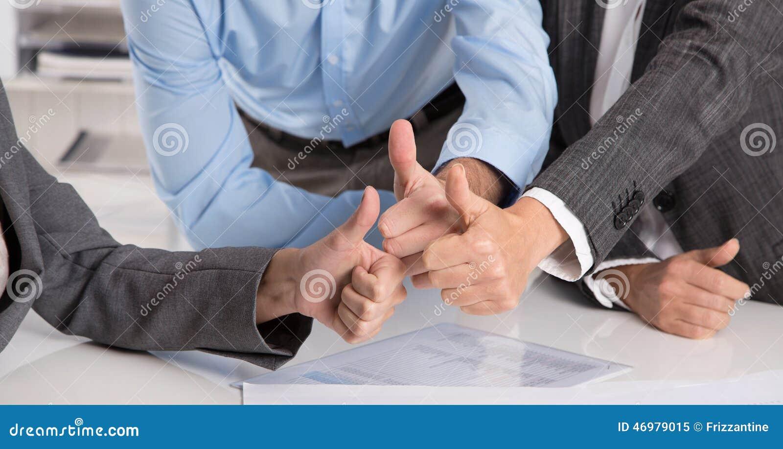 Pojęcie dla pomyślnej pracy zespołowej: ludzie biznesu robi kciukom u