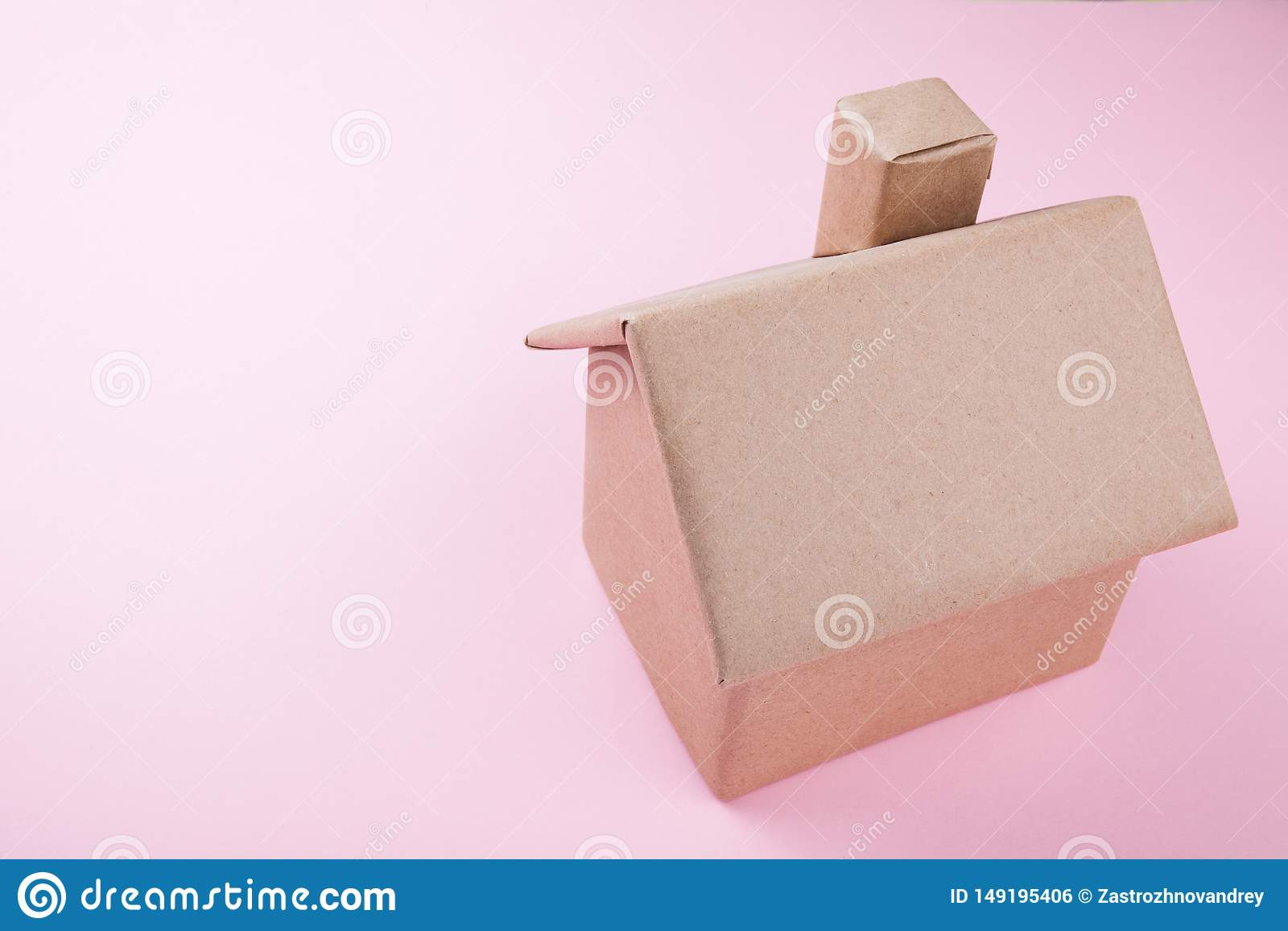 Pojęcie, dom robić panwiowy karton na różowym tle, odizolowywający miejsce tekst