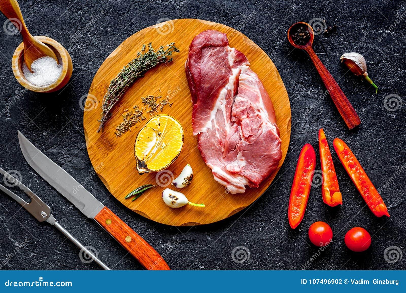 Pojęcie kulinarny mięsny stek na ciemnego tła odgórnym widoku