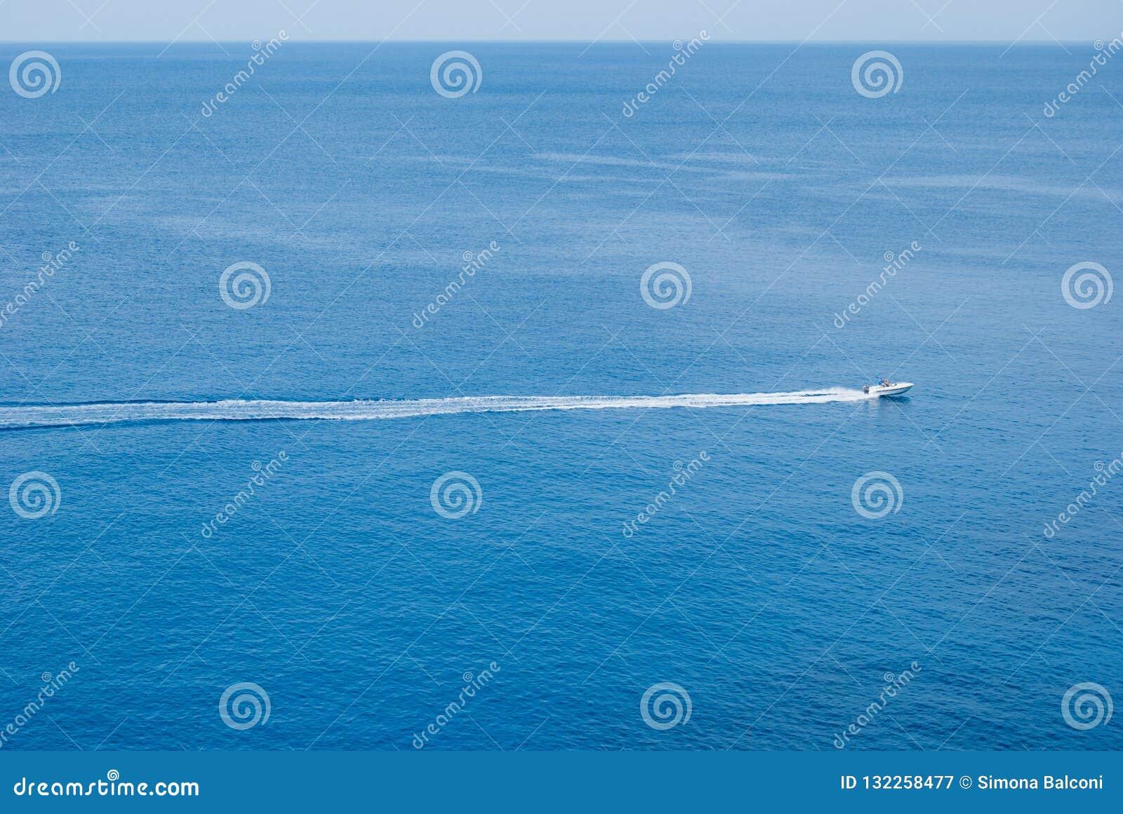 Pojedyncza biała motorowa łódź z długim śladem za