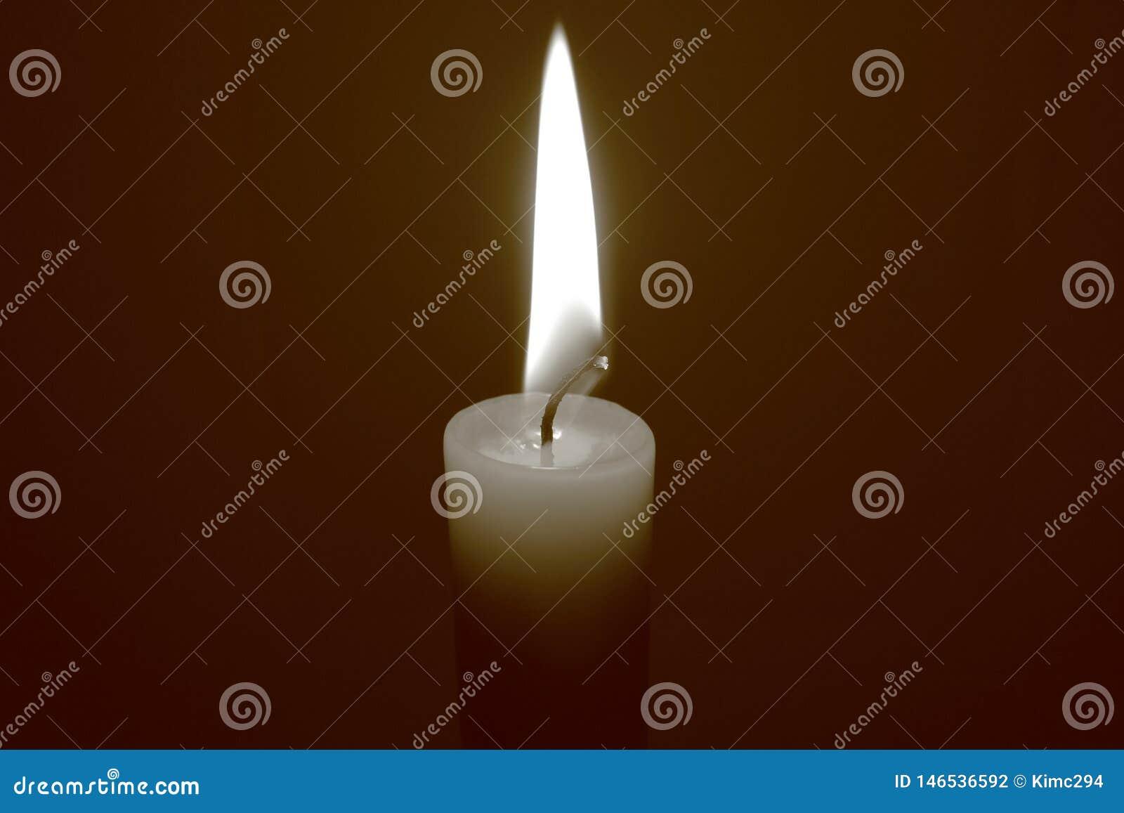 Pojedyncza płonąca świeczka na ciemnym tle Sepiowy brzmienie