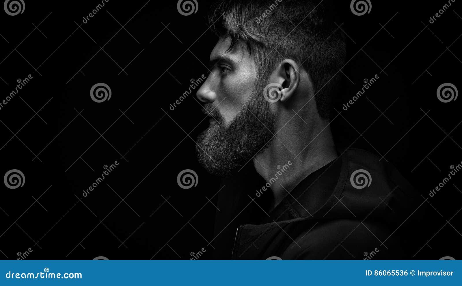 Pojedyncza pozycja w profilowym młodym przystojnym poważnym brodatym mężczyzna wewnątrz