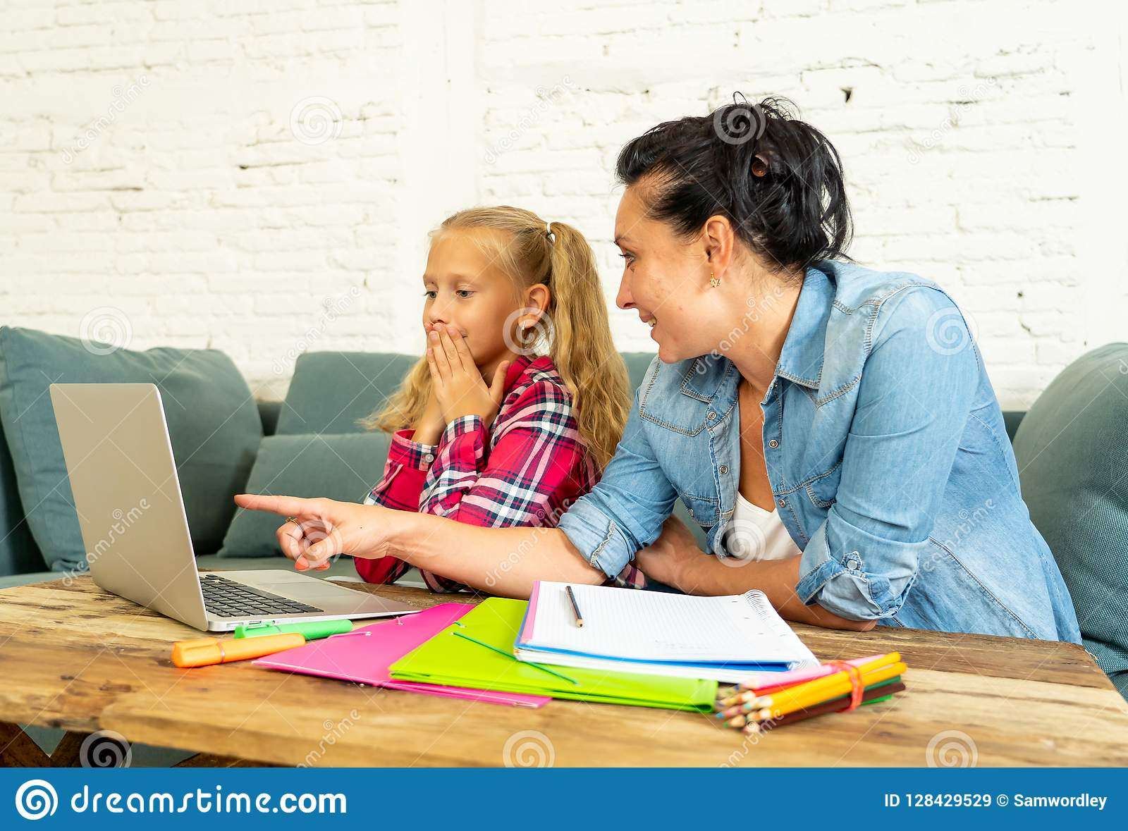 Pojedynczy mum pomaga jej córki robi jej pracie domowej z laptopem w domu