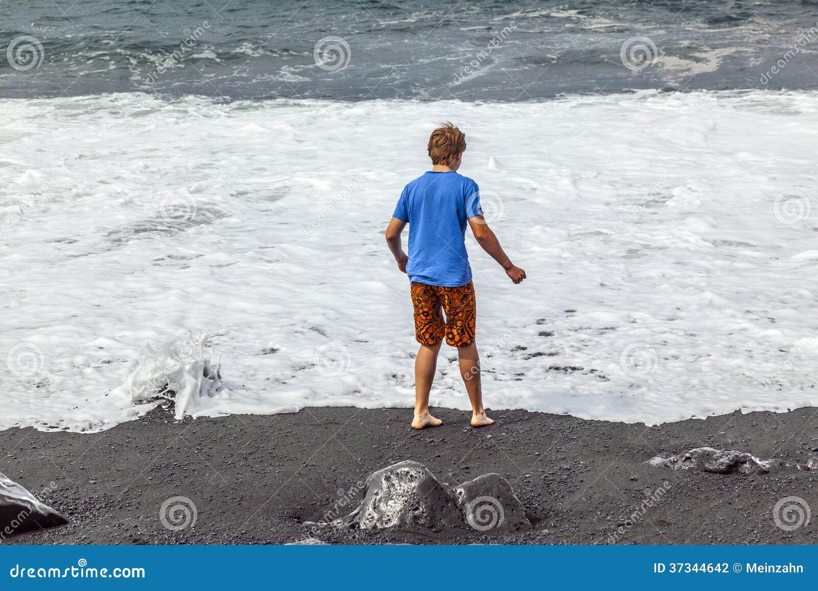 Pojkar har gyckel på den svarta stranden