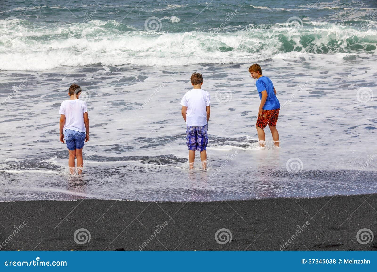 Pojkar har gyckel på den svarta vulkaniska stranden