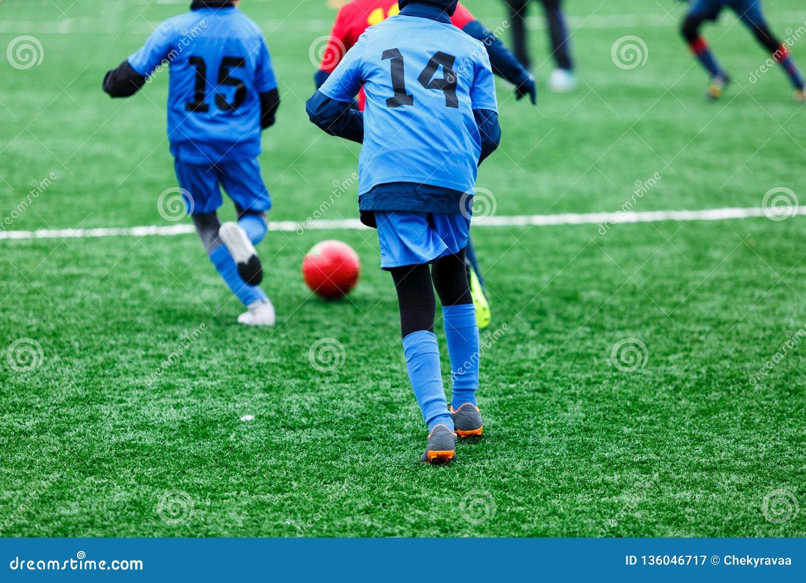 Pojkar i röd och blå sportswear spelar fotboll på fält för grönt gräs Ungdomfotbolllek Barnsportkonkurrens, ungar spelar