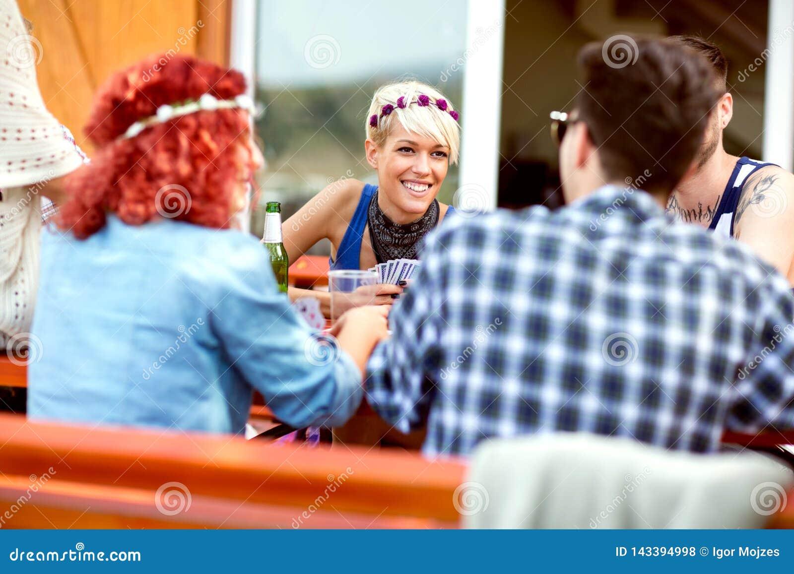 Pojkar och flickor har gyckel medan spela kort i den utomhus- restaurangen