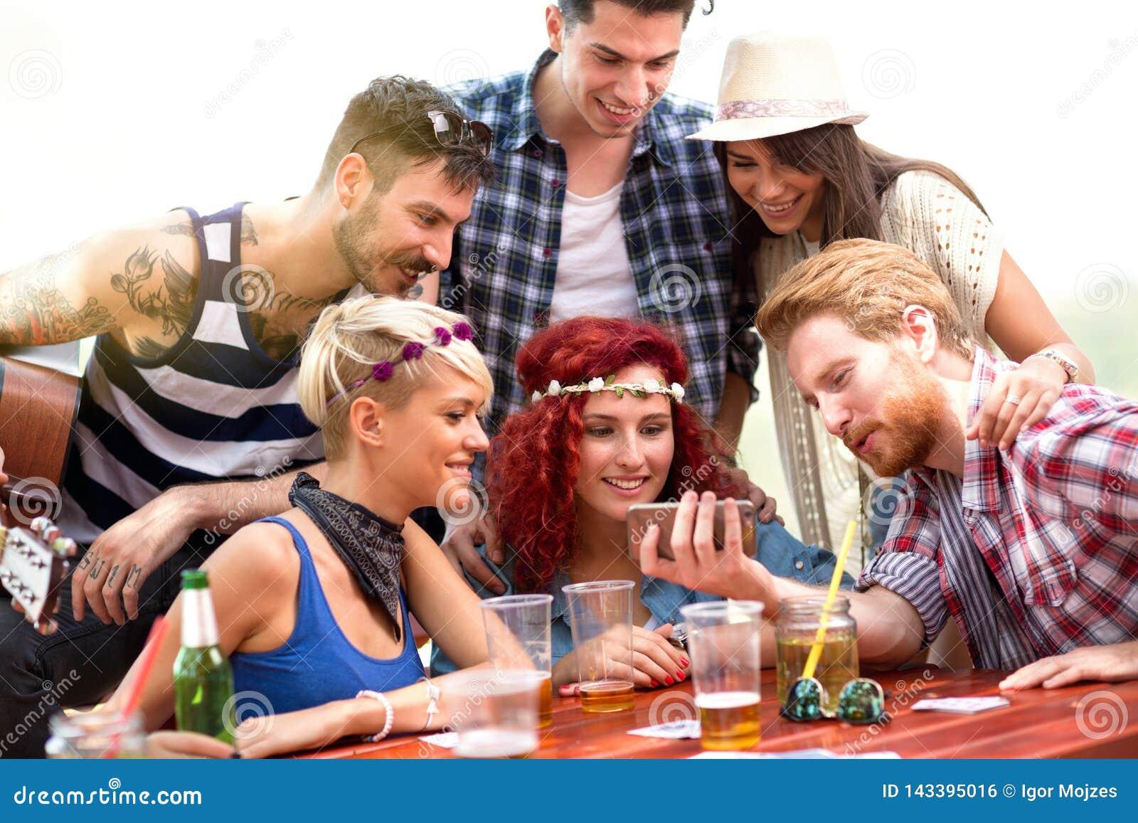 Pojkar och flickor på picknick i naturen som har gyckel, medan hålla ögonen på foto på mobiltelefonen