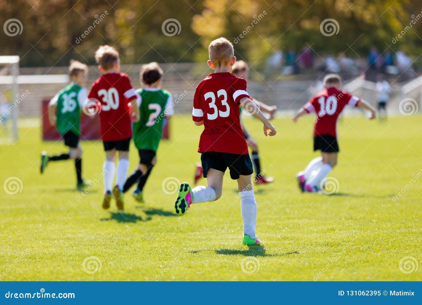 Pojkar som sparkar fotboll på sportfältet En handlingsportbild av en grupp av ungar som spelar leken för fotbollfotbollturnering