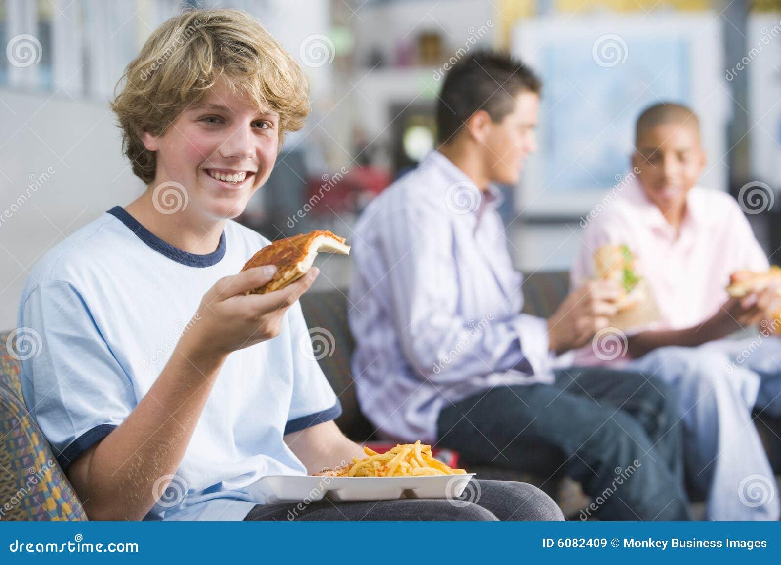 Pojkar som tycker om snabbmat, äter lunch tonårs- tillsammans