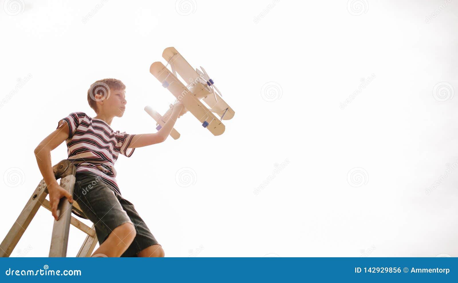 Pojke överst av en stege med leksakflygplanet