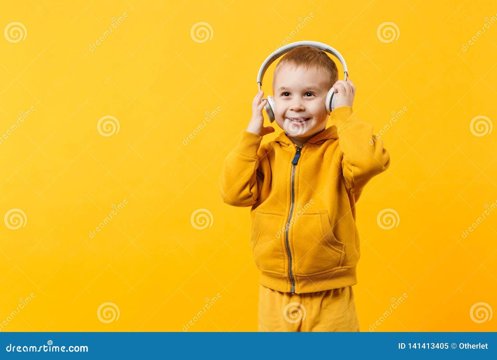 Pojke för liten unge 3-4 år gammal bärande gul kläder i hörlurar som isoleras på orange väggbakgrund, barnstudio