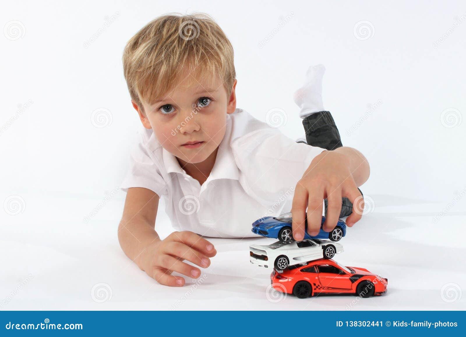 Pojke för litet barn som satisfyingly spelar med hans leksaker och bygger ett torn av bilarna