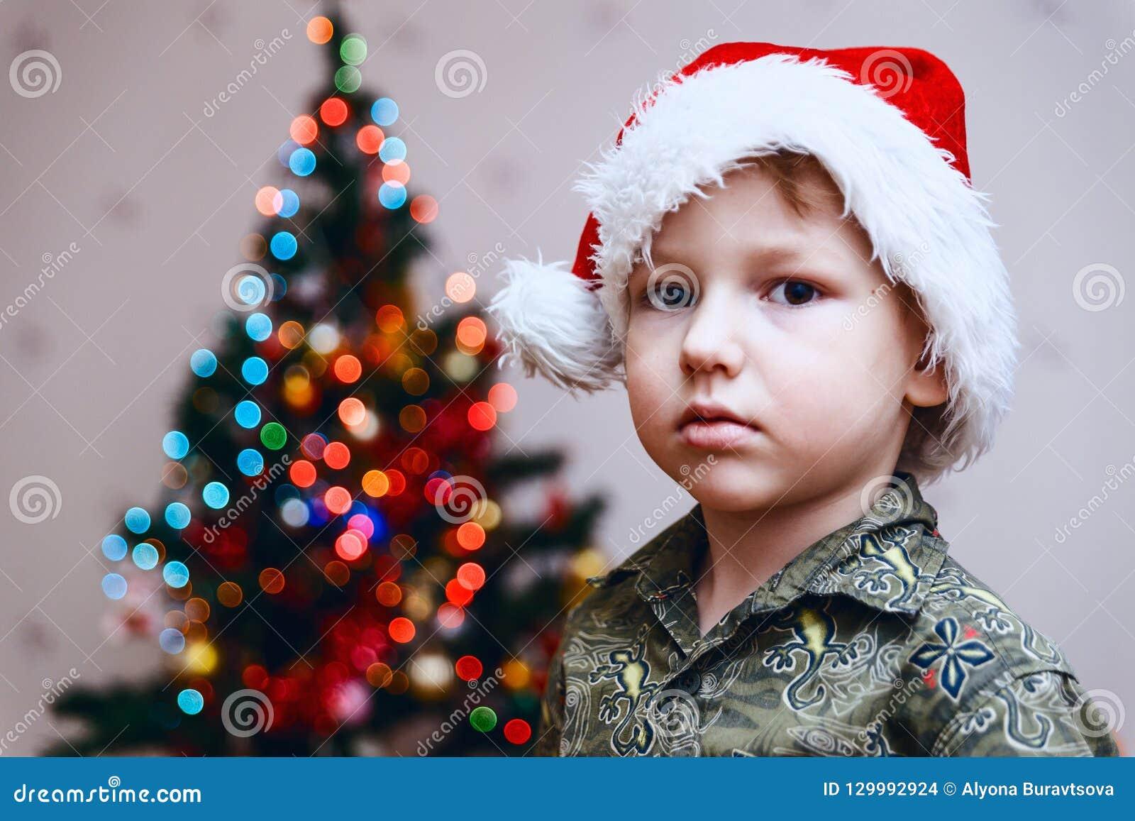Pojke i jultomten lock på julgranbakgrund