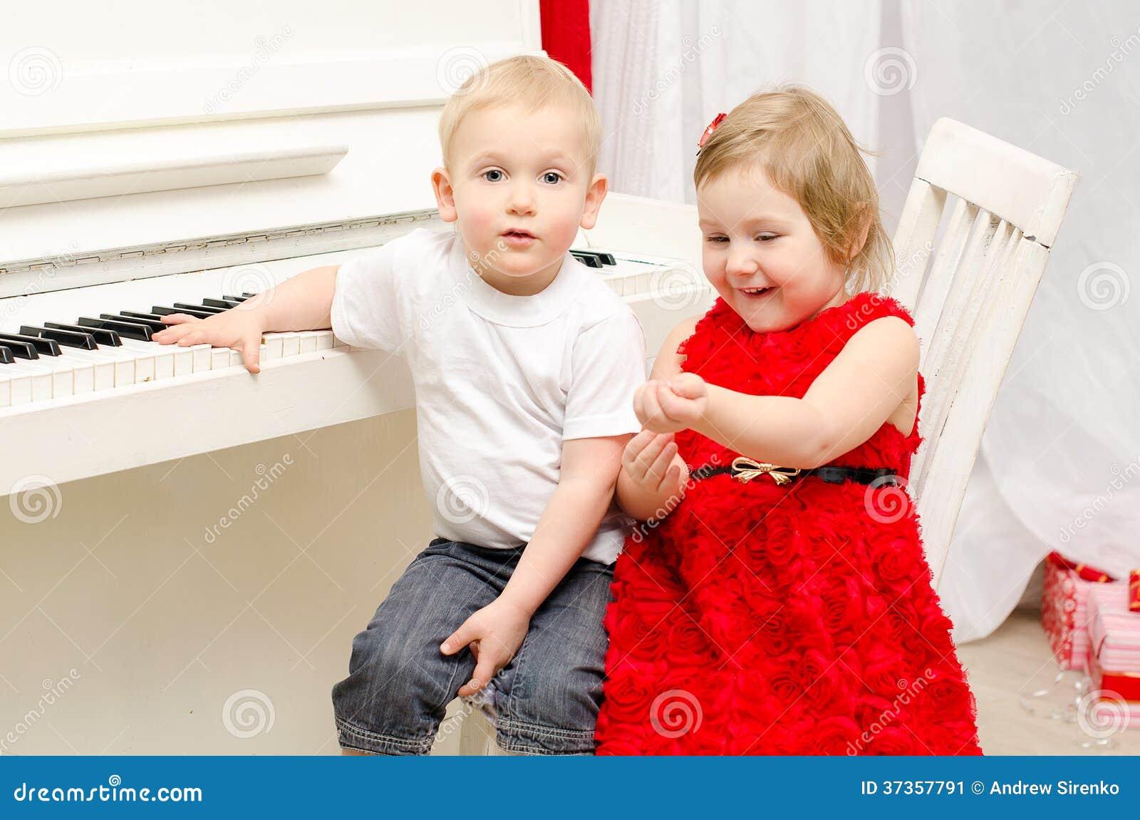 Pojke med flickan som sitter nära det vita pianot