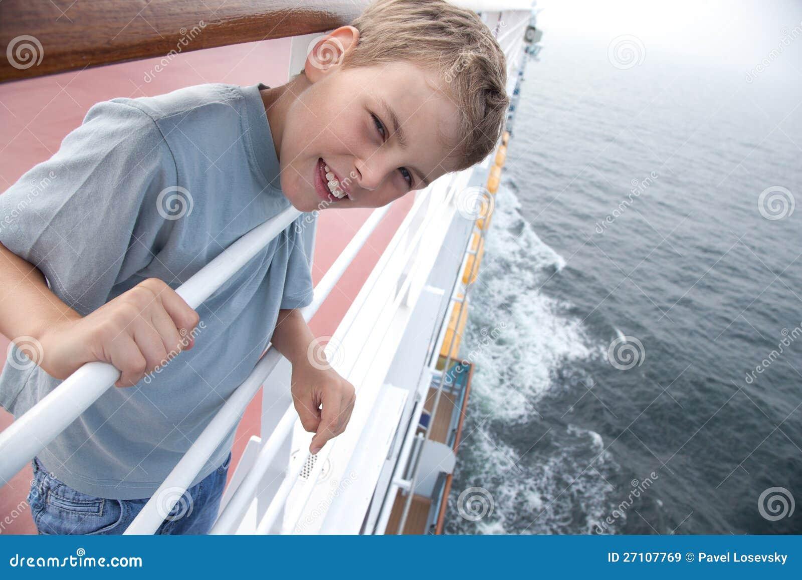 Pojke nära handrails på däck av shipen